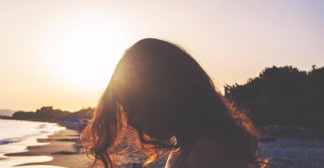 silhouette of woman standing in sunlight near shoreline