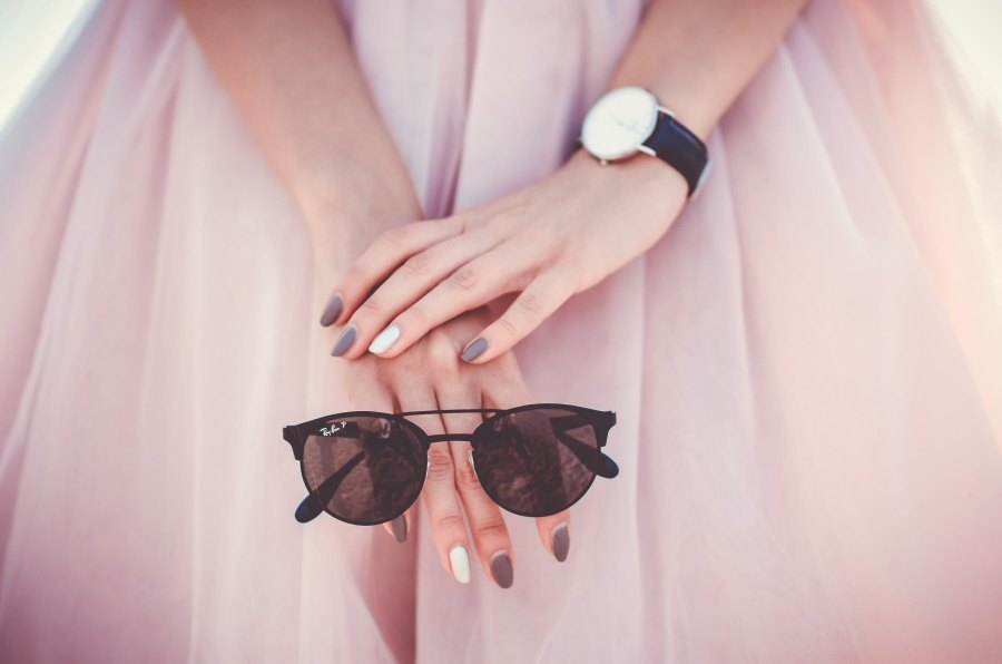 pink dress with woman's hands in front, holding sunglasses