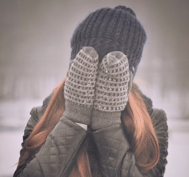girl covering eyes with glove-covered hands