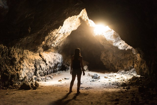 Girl standing in cave, near spot where sunlight is shining through