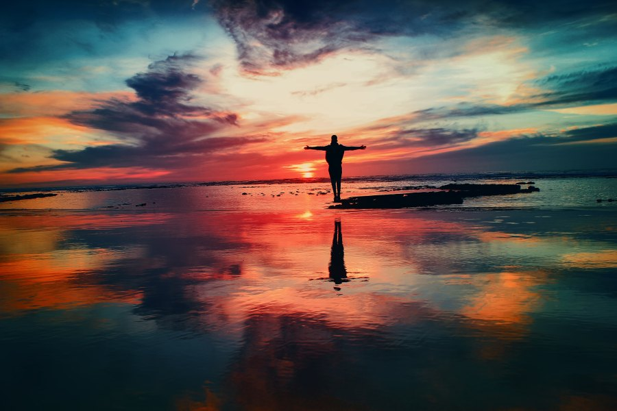 happy person standing on water in colorful sunset